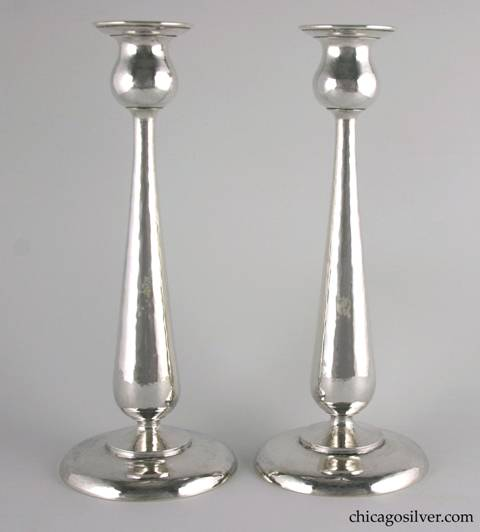 "Kalo candlesticks, pair, in tall tulip form with broad round base and tapered, shaped stem with flaring bulb shaped cup.  Hammered all over.  Engraved on the underside ""Christmas 1923"".  10-3/8"" H and 4-5/8"" W at base.  Marked:  STERLING / HAND WROUGHT / AT / THE KALO SHOP / G152L"