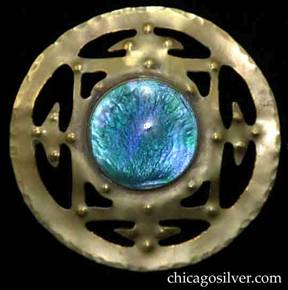 Forest Craft Guild brooch, round, large, brass, with extensive cutouts forming an inside square with interior cutouts in the corners and arrow-shaped connectors between the middle of each side of the square and the outer rim of the circle.  In the center is a round bezel-set iridescent blue-green glass cabochon stone.  On the surface of the interior are numerous small repousse dimples, and the outer edge of the circle is heavily hammered.  The entire brooch is slightly convex.