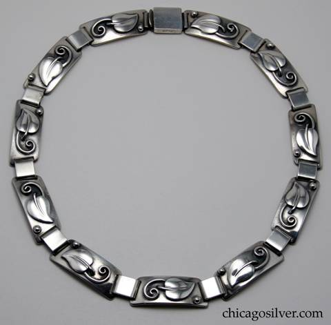 Laurence Foss necklace / choker, composed of eleven graduated trapezoidal links, each with an applied leaf with curving stem and separate bead, joined to the others by thick silver loops.  Spring clasp.