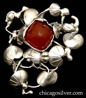 Mary Gage pin, composed of freeform open wirework frame holding arrangement of chased and hammered lily pads and silver beads, surrounding a square carved square cabochon bezel-set carnelian stone