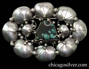 Mary Gage pin, large oval, composed of eight chased lily pads centering two smaller pads that flank a trapezoidal turquoise bezel-set stone