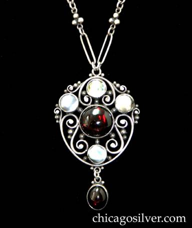 Frank Gardner Hale pendant on chain, stylized shield form frame with handwrought sterling scrolls and beads with a round, central garnet cabochon with three bezel-set blister pearls above and one below finished with a garnet drop.  Original paper clip chain with oval links alternating with 3 bead clusters, toggle clasp.