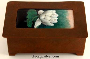 Frank Gardner Hale box, copper, rectangular, on four small applied feet at the corners with curved edges, hinged overlapping lid with rounded corners and large enameled rectangular domed insert in excellent condition.  Enameled decoration is detailed creamy white water lily blossom above rich green leaf, on background that varies from deep black at the bottom to mottled green and then light rose at the top.  Nicely hammered.