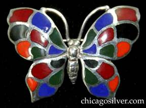 Kalo brooch / pin, butterfly-shaped, with detailed insect body and antennae surrounded by four-part wings decorated with cloisonné enamel cells in blue, orange, black, red, and green colors