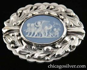 Kalo brooch, oval, dimensional, with scalloped outside frame and smaller oval inside frame centering an oval piece of blue bezel-set Wedgwood with classic motif