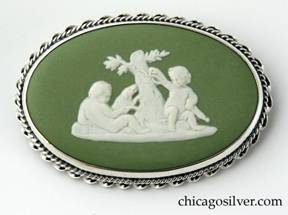 Kalo brooch, oval frame open on the back, with gadrooned twisted cable border decoration, centering a piece of green bezel-set Wedgwood with classic motif