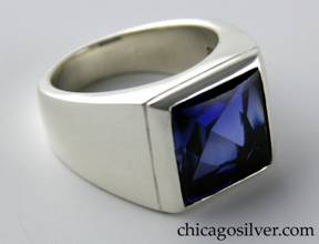 Kalo ring, silver, thick and heavy, square front centering faceted blue stone with chased line around edge, round wide shank, small square cutout behind stone.