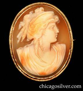Lebolt brooch, carved bezel-set shell cameo of woman in classical clothing looking to the right, with tan background, inside oval gold frame with applied ropelike decoration around outside