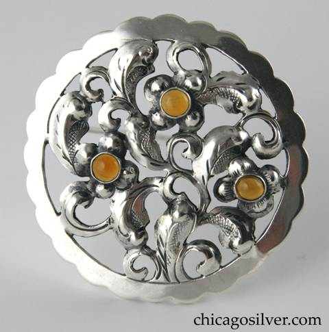 Yngve Olsson round brooch with chased and cutout details and three amber stones
