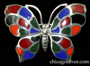 Kalo brooch, butterfly-form, with detailed insect body and antennae surrounded by four-part wings decorated with cloisonné enamel cells in blue, orange, black, red, and green colors