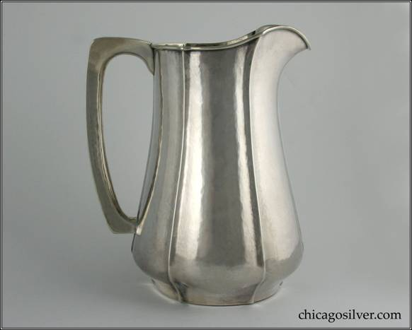 "Kalo pitcher, water, with flat bottom, applied wire on rim and fluted sides, nice angular hollow handle.  Hammered surfaces.  Duplicate form to one shown full page (#49) in Sharon Darling's ""Chicago Metalsmiths"" book.  7"" W and 8-1/2"" H.  STERLING / HANDWROUGHT / AT / THE KALO SHOP / 10"