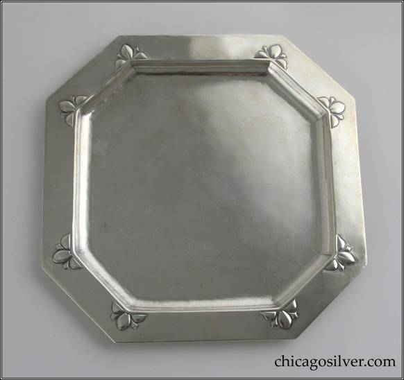 Kalo tray, octagonal, round, with flat bottom, alternating long and short sides and a slightly raised border with repoussé stylized floral design at each of the eight corners