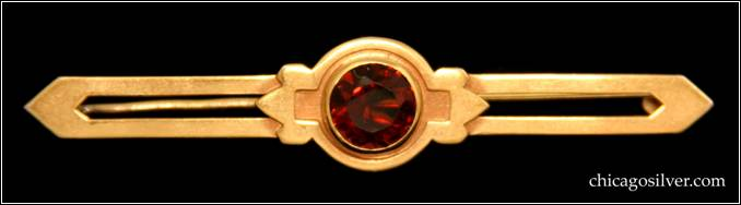 "Kalo bar pin, gold, small, centering round faceted bezel-set garnet, with recessed area around stone that has square-shaped extensions on the sides surrounded by pointed details, with two long arms that have cutouts in the middle and points at the end.  2-1/2"" L and 1/2"" H.  Marked KALO 14K"