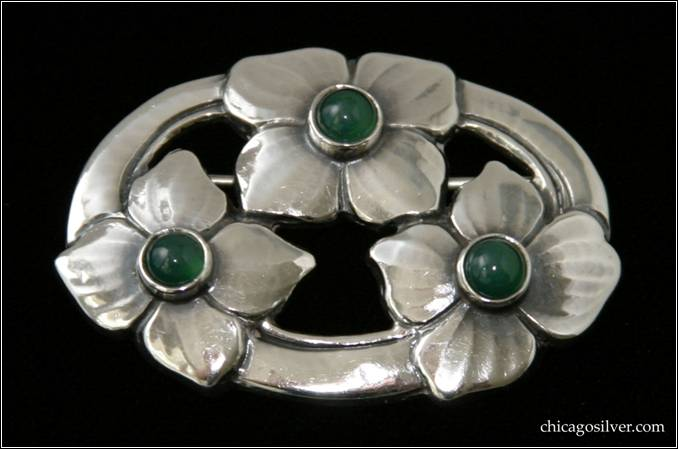 "Kalo brooch / pin, oval, three large blossoms spaced evenly around a chased and cutout oval frame, each with four petals and each centering a dark green bezel-set round cabochon stone.  Nice hammering -- the blossoms have subtle texture lines extending from the center outward that are the result of delicate hand work.  1-7/8"" L and 1-1/4"" W.  Marked:  STERLING KALO"