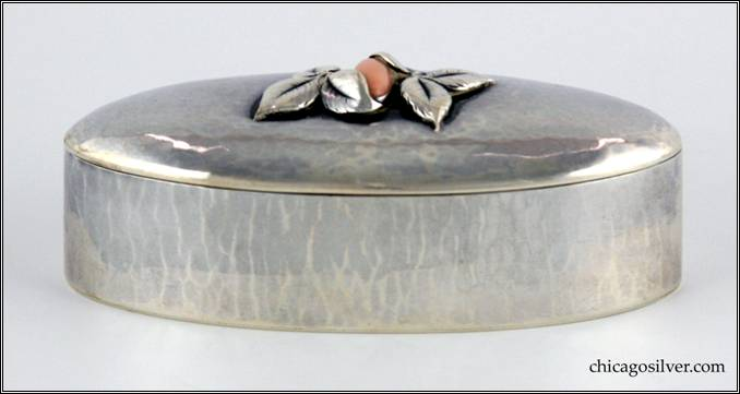 "Kalo box, oval, covered, slender, with domed cover which has a bezel-set cabochon of pink coral flanked by two clusters of leaves.  Hammered surfaces with elongated hammer marks on the sides.  3-1/2"" W and 1-3/8"" H.  Marked:  STERLING / KALO"