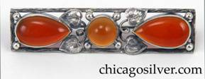 Brooch, silver, rectangular frame with orange translucent tear-shaped bezel-set cabochon stones and a similar round stone at center, with leaves, curling silver stems and silver bead ornament.  Frame is worked to look like wood grain.