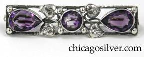 Brooch, silver, rectangular frame with two tear-shaped bezel-set faceted amethyst stones at the ends and a similar round stone at center, with leaves, curling silver stems and silver bead ornament.   Worked frame.